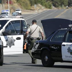 A police official carries a weapon in front of the Maplewood Apartments after a shooting in Lakeside, Calif., Tuesday, Sept. 25, 2012. The San Diego County sheriff's Capt. Duncan Fraser said two deputies and a suspect have been shot while the deputies were trying to contact a child abuse suspect at the suburban apartment complex.