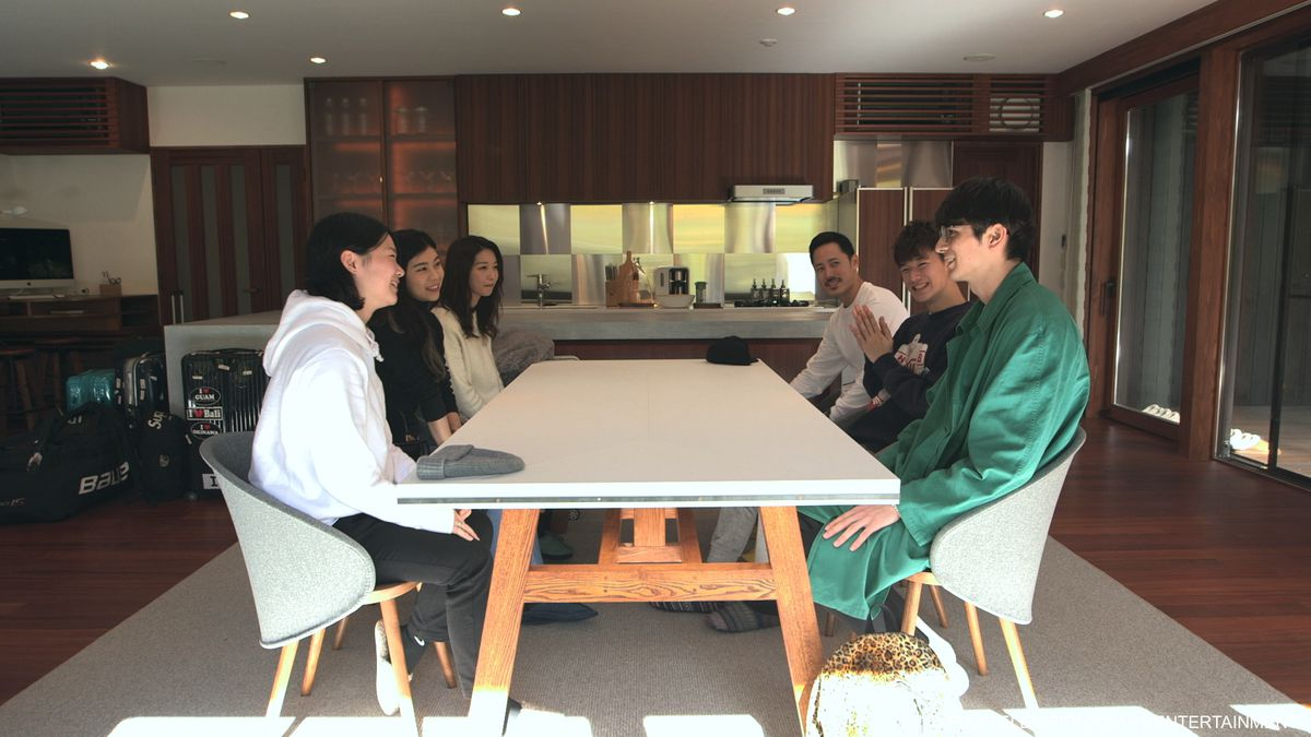 Celebrity Beauty: Six young people sit around a rectangular table in a spacious living room. They are smiling and seemingly enjoying each others' company.