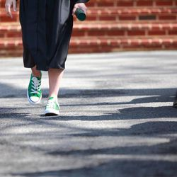 A Southern Virginia University graduate walks with her diploma in hand and the school's unofficial shoes--green Converse Chuck Taylor All-Stars--on her feet at commencement exercises on April 27, 2013.