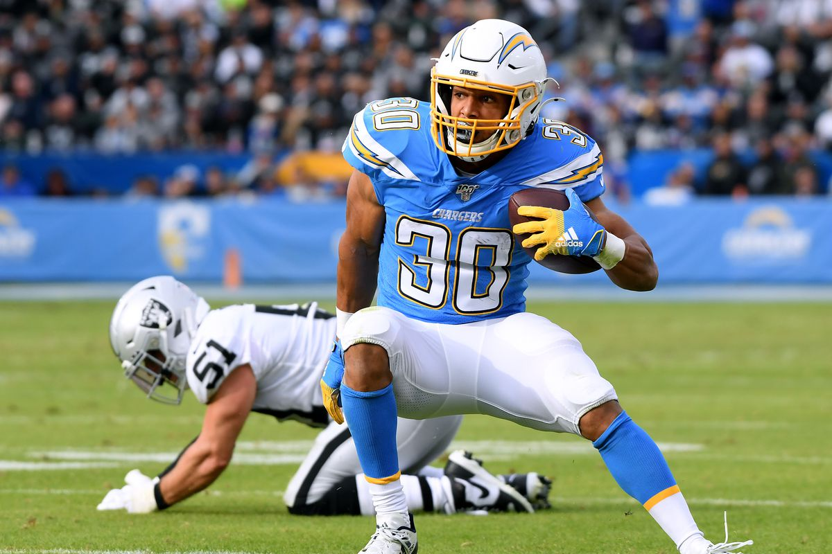 Austin Ekeler #30 of the Los Angeles Chargers cuts back after breaking a tackle from Will Compton #51 of the Oakland Raiders during the second quarter at Dignity Health Sports Park on December 22, 2019 in Carson, California.