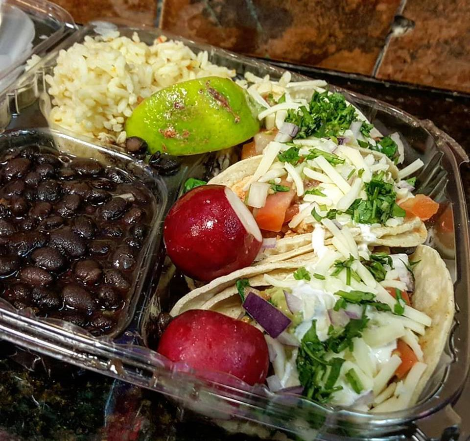 Plastic takeout container with three tacos, rice with a lime wedge, black beans, and radishes for garnish