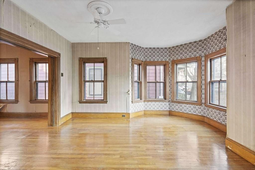 A large, empty room with several windows, and some bow out, and there's an entryway to another large, empty room.