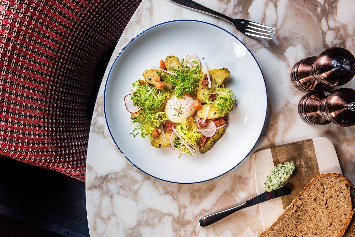 A Lyonnaise salad from Brasserie Liberte with bacon lardons, poached egg, potato, frisee, radishes, and brown butter bacon vinaigrette