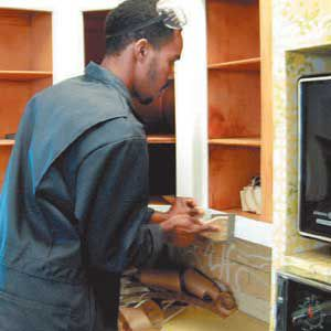 <p>Homeowners have their choice of laminates, rigid thermofoils or wood veneer as a refacing material. Here, Trevor from Kitchen Tune-Up uses a smoothing tool to set the bond on rigid thermofoil.</p>