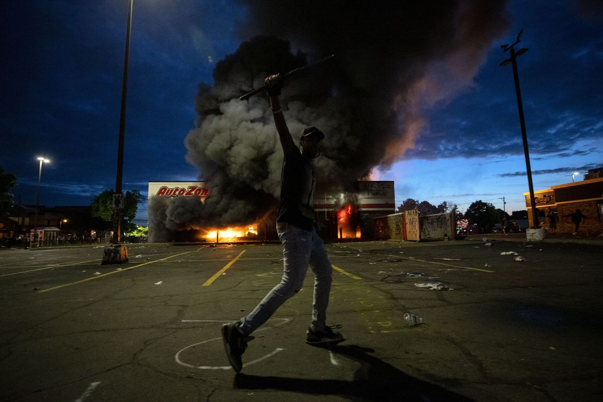 A man poses for a photo in the parking lot of an AutoZone store in flames, while protesters hold a rally for George Floyd in Minneapolis on Wednesday, May 27, 2020.