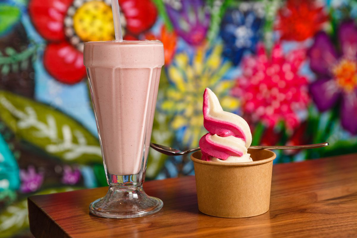 A strawberry oat milk shake stands on the left, while a cup of vanilla-beet ice cream swirl sits on the right