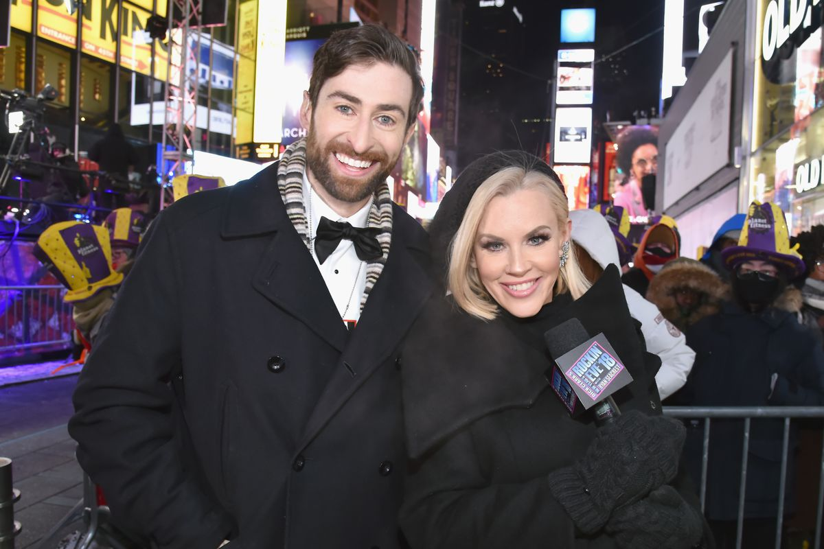 HQ Trivia host Scott Rogowsky wears black tie outside at Times Square with New Year's Eve host Jenny McCarthy