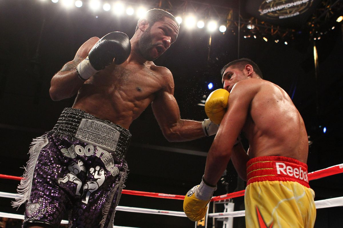 WASHINGTON, DC - DECEMBER 10:  Lamont Peterson punches Amir Khan during their WBA Super Lightweight and IBF Junior Welterweight title fight at Washington Convention Center on December 10, 2011 in Washington, DC.  (Photo by Al Bello/Getty Images)