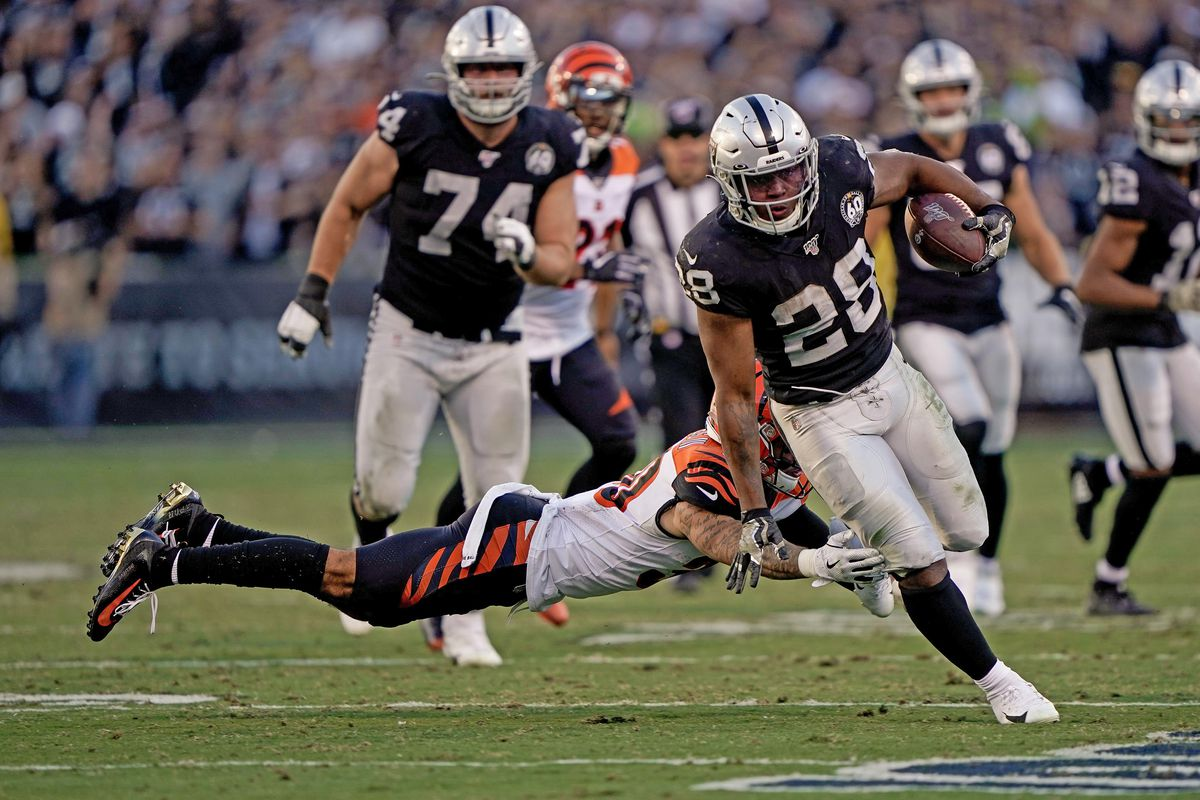 Oakland Raiders running back Josh Jacobs dodges Cincinnati Bengals free safety Jessie Bates during the fourth quarter at the Oakland Coliseum.