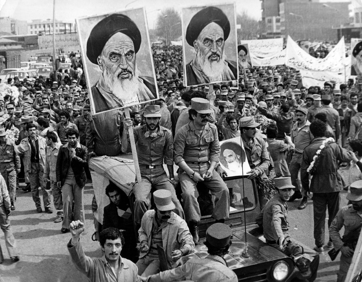 The Iranian Islamic Republic Army demonstrates in solidarity with people in the street during the 1979 Iranian Revolution. They are carrying posters of the Ayatollah Khomeini, the Iranian religious and political leader.