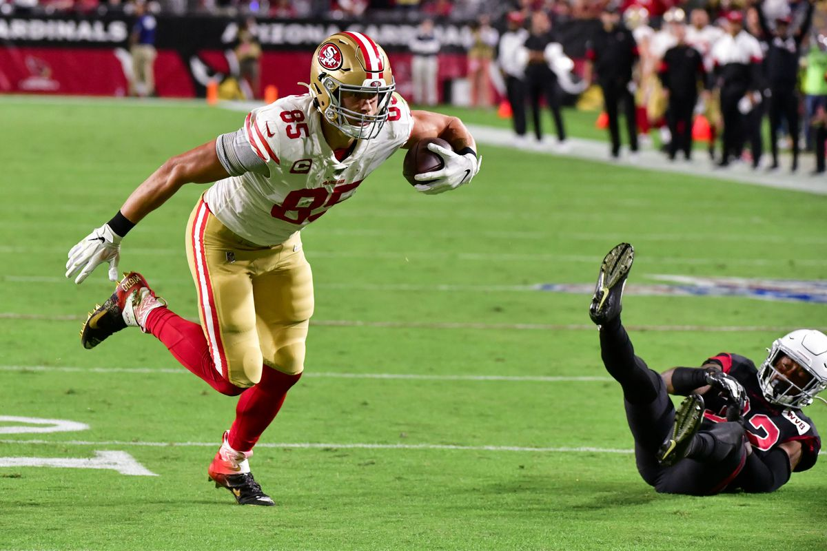 San Francisco 49ers tight end George Kittle knocks over Arizona Cardinals safety Budda Baker while running for a touchdown in the first quarter at State Farm Stadium.