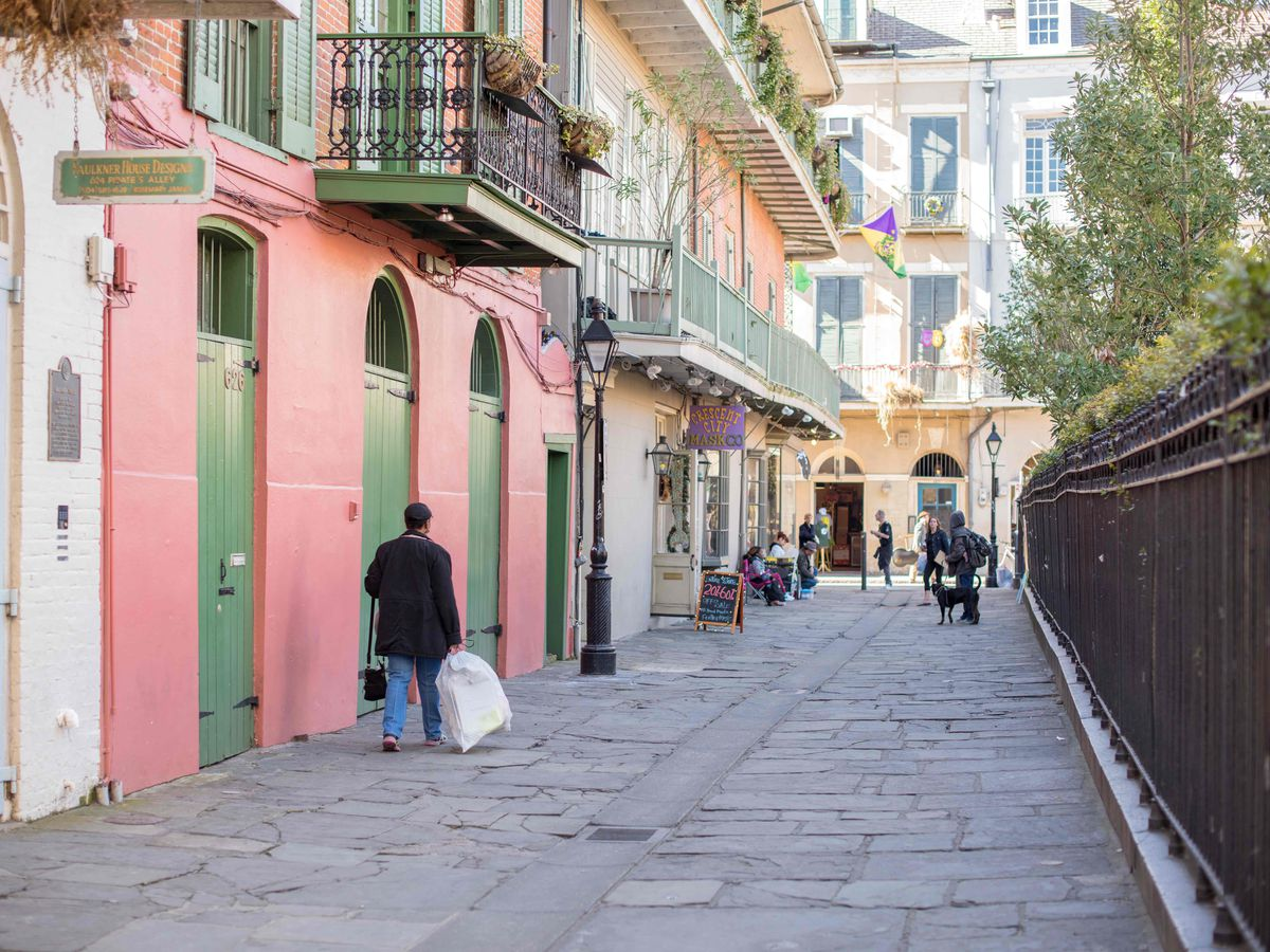 An alley next to a row of colorful houses in New Orleans. One of the houses is pink with green doors. There are balconies on the houses. There is a fence on the other side of the alley.