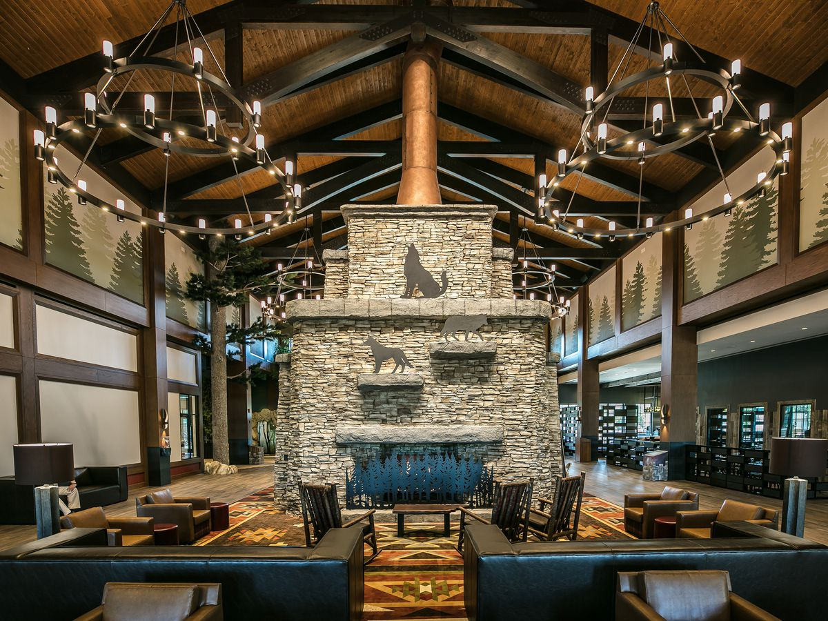 The interior of a lodge. There are couches, tables, and large chandeliers hanging from the wooden ceiling. There is a fireplace.