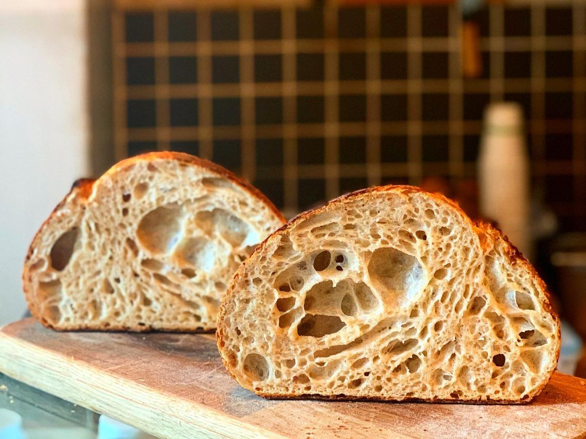 A loaf of bread sliced in half and displayed on a wooden panel to reveal the crumb inside