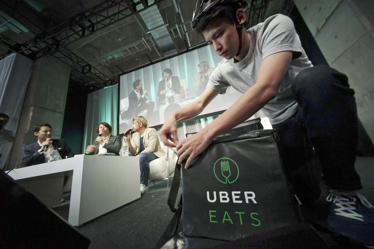 A delivery man brings food during a press conference of UberEats in Tokyo, Wednesday, Sept. 28, 2016. UberEats is one of many food delivery services offering food from restaurants and grocery delivery during the COVID-19 pandemic.