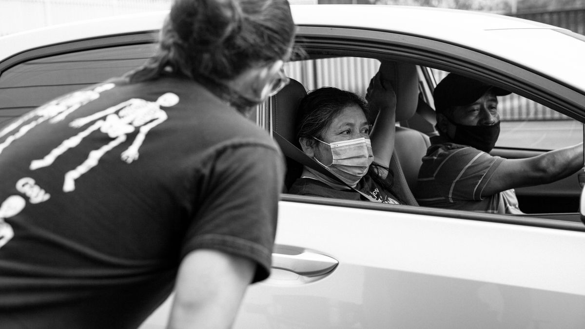 Black and white photo of a woman looking into the open passenger side's window of a car; a man and woman sit in the front of the car.