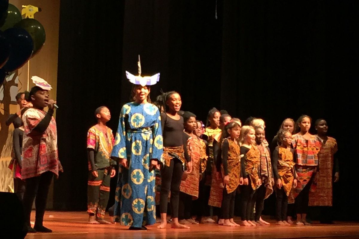 Fifth grader Arael Stigler (left with the microphone) performs the role of Rafinki from the musical The Lion King.