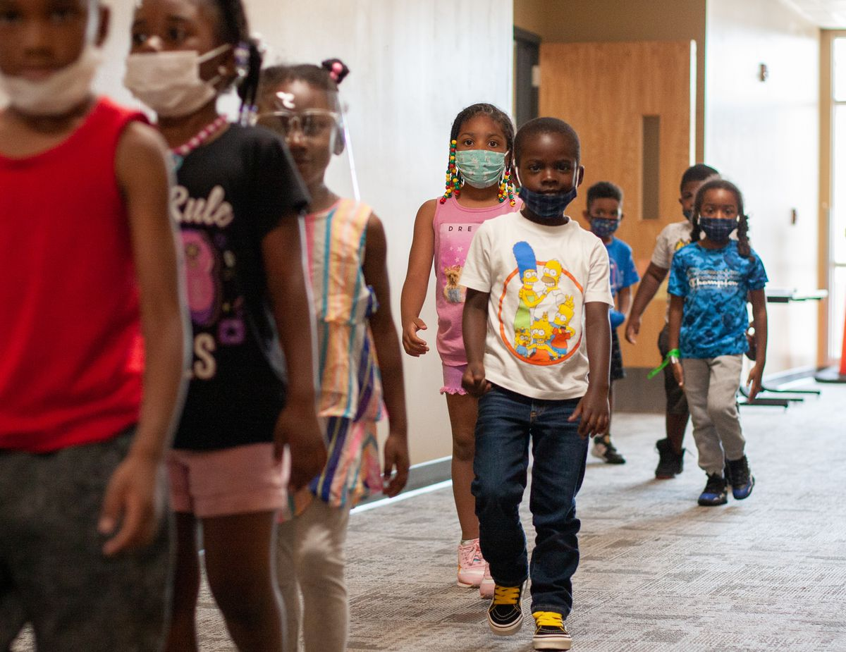 Eight kids, all wearing masks or face shields, walk in a jumbled line through a carpeted school hallway