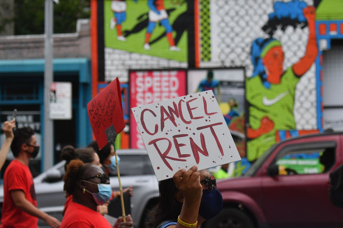 """A protester holds up a sign that reads, """"Cancel rent."""""""