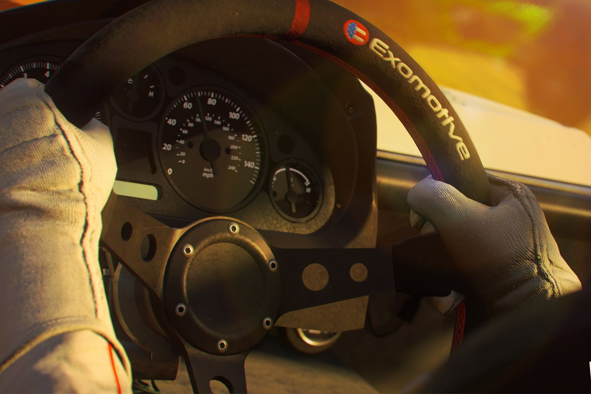 Close up of a driver's gloved hands on the wheel of a rally car