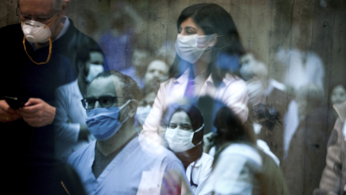 Health care workers wearing masks and sitting listening to a concert.