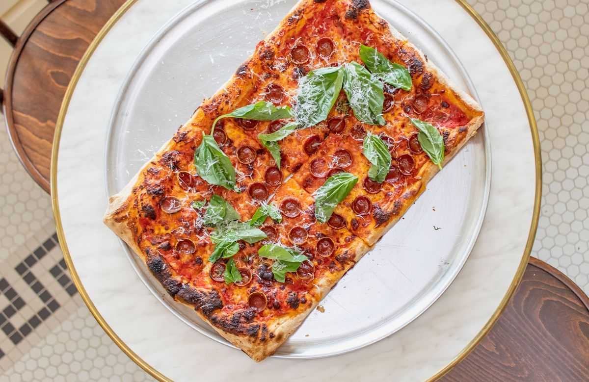 An overhead photograph of a square pepperoni pizza with sprigs of basil