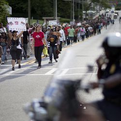 A march passes a police officer on a  motorcycle at right during a protest the day after George Zimmerman was found not guilty in the 2012 shooting death of teenager Trayvon Martin, Sunday, July 14, 2013, in Atlanta. (AP Photo/David Goldman)