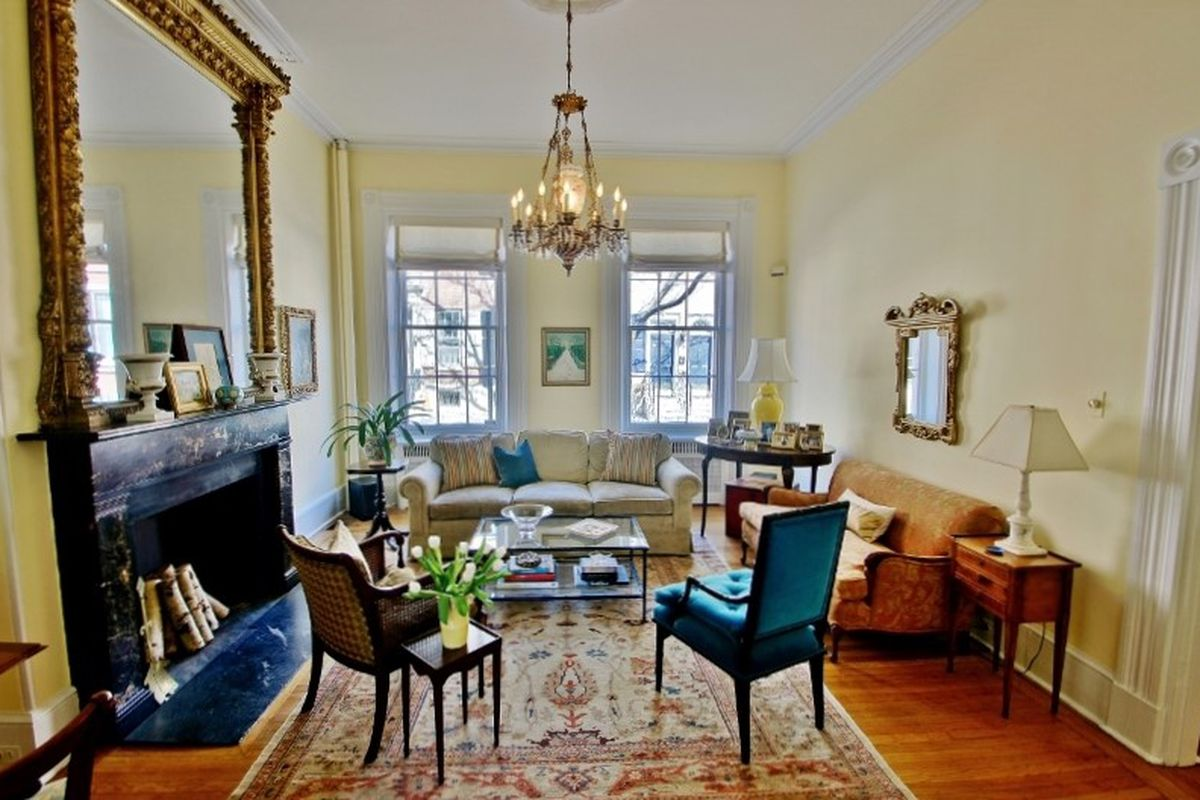 A stately living room with a fireplace and gold-leafed mirror and chandelier.