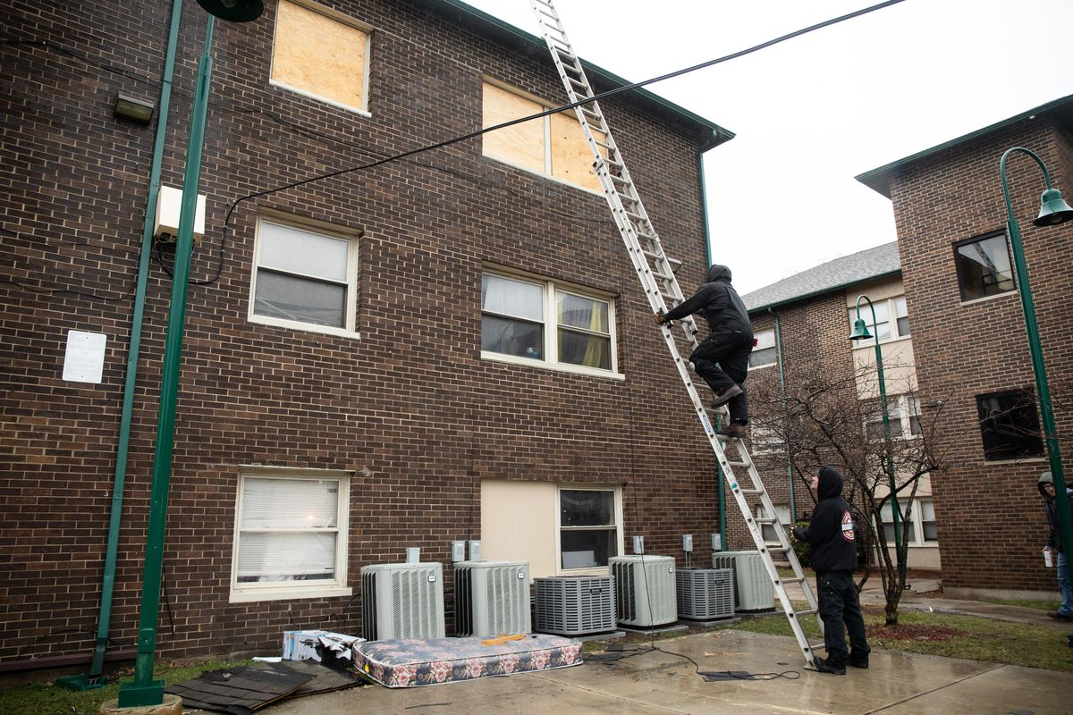 Crews board up windows Thursday morning at an apartment in the 6100 block of South Wabash Avenue after it caught fire overnight in Washington Park.