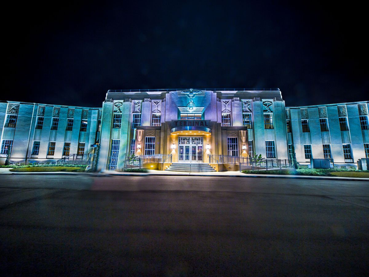 The exterior of Lakefront Airport. The facade is illuminated with colorful lights.