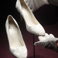 LONDON - JULY 20:   The Duchess of Cambridge's bridal shoes are photographed before they go on display at Buckingham Palace during the annual summer opening on July 20, 2011 in London, England. The ivory size five and a half shoes show slight signs of wea