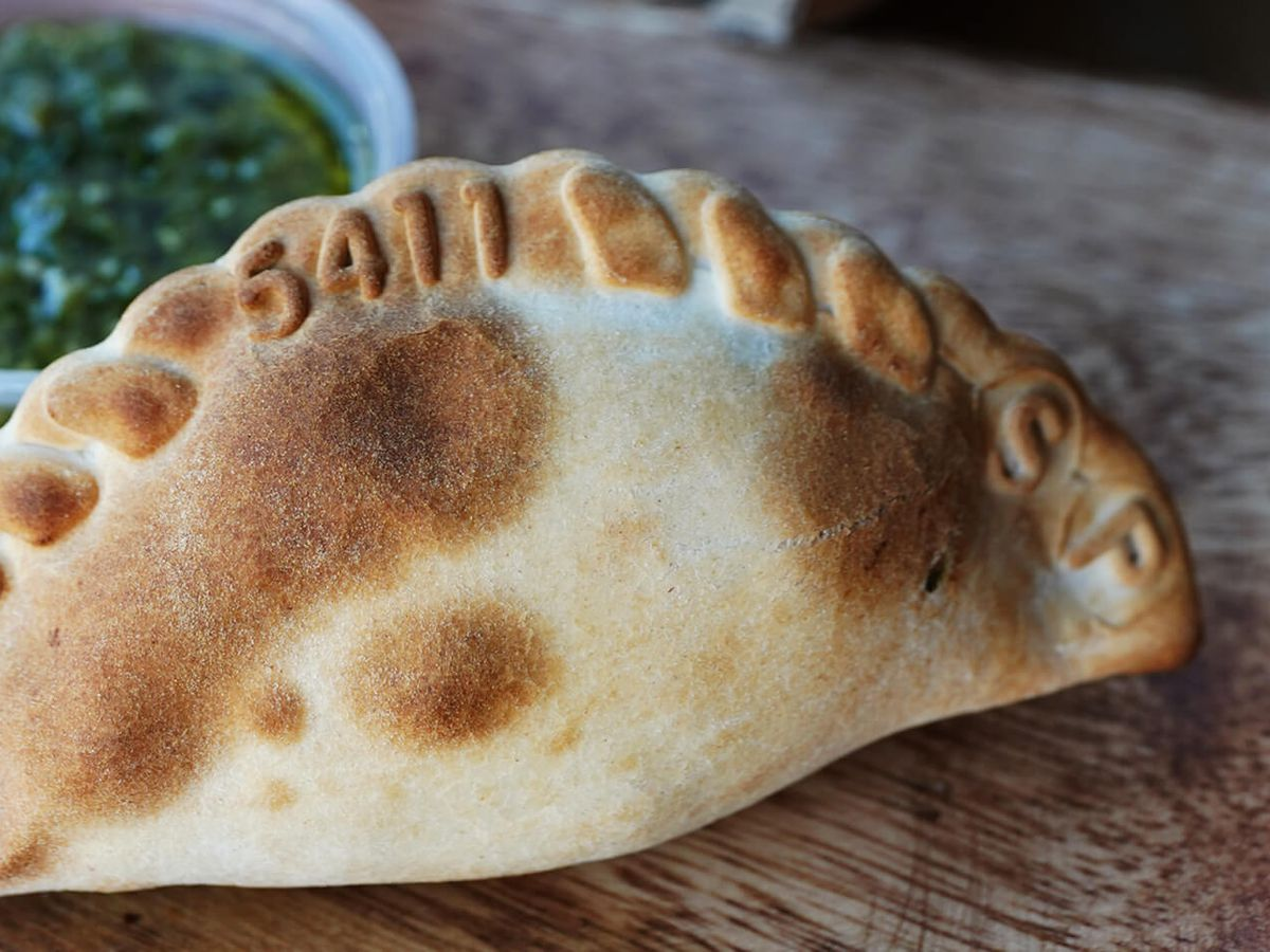 A baked empanada with chimichurri sauce on the side