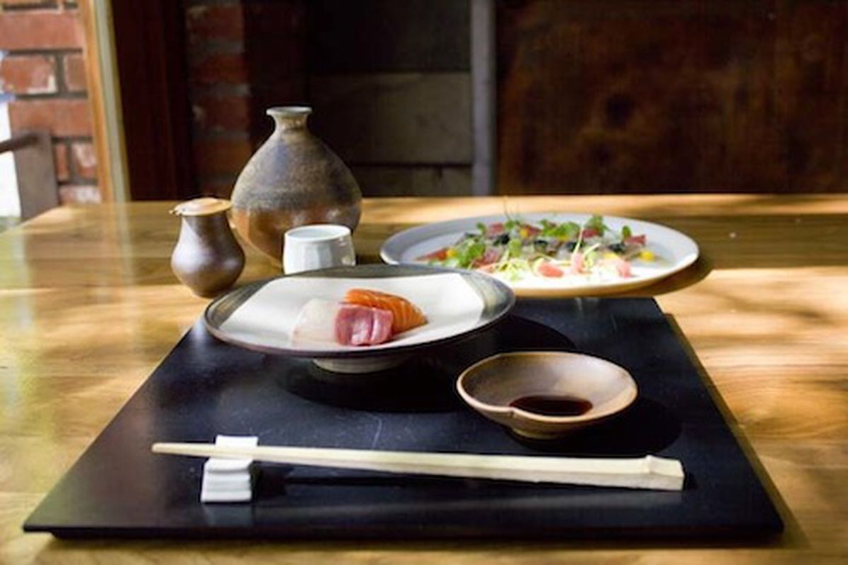 Sushi with soy sauce, chopsticks, and sake vessels