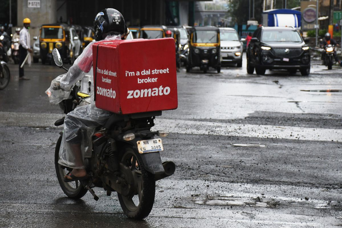 A Zomato delivery man seen riding along the streets of...