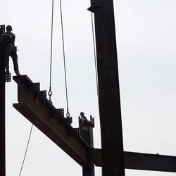 """In this March 23, 2012, photo ironworkers connects steel beams at the top of One World Trade Center in New York. One World Trade Center, the giant monolith being built to replace the twin towers destroyed in the Sept. 11 attacks, will lay claim to the title of New York City's tallest skyscraper on Monday, April 30, as workers erect steel columns that will make its unfinished skeleton a little over 1,250 feet, just high enough to peak over the observation deck on the Empire State Building. The milestone is a preliminary one. The so-called """"Freedom Tower,"""" isn't expected to reach its full height for at least another year, at which point it is likely to be declared the tallest building in the U.S."""