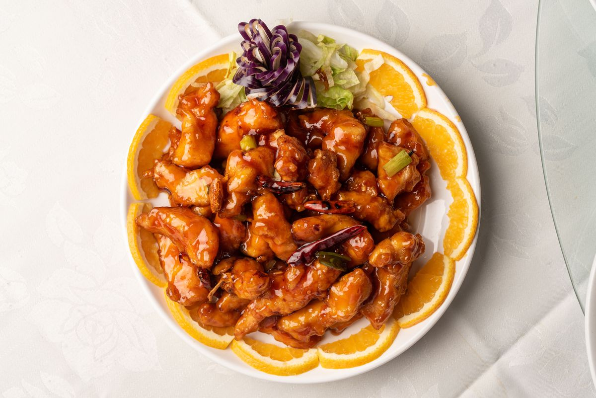 A plate of chicken glazed in a glossy orange sauce with halved orange slices lining the platter.