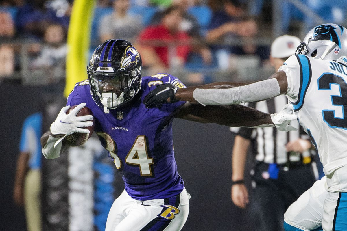 Baltimore Ravens running back Ty'Son Williams (34) with the ball as Carolina Panthers defensive back Jalen Julius (35) defends in the third quarter at Bank of America Stadium.