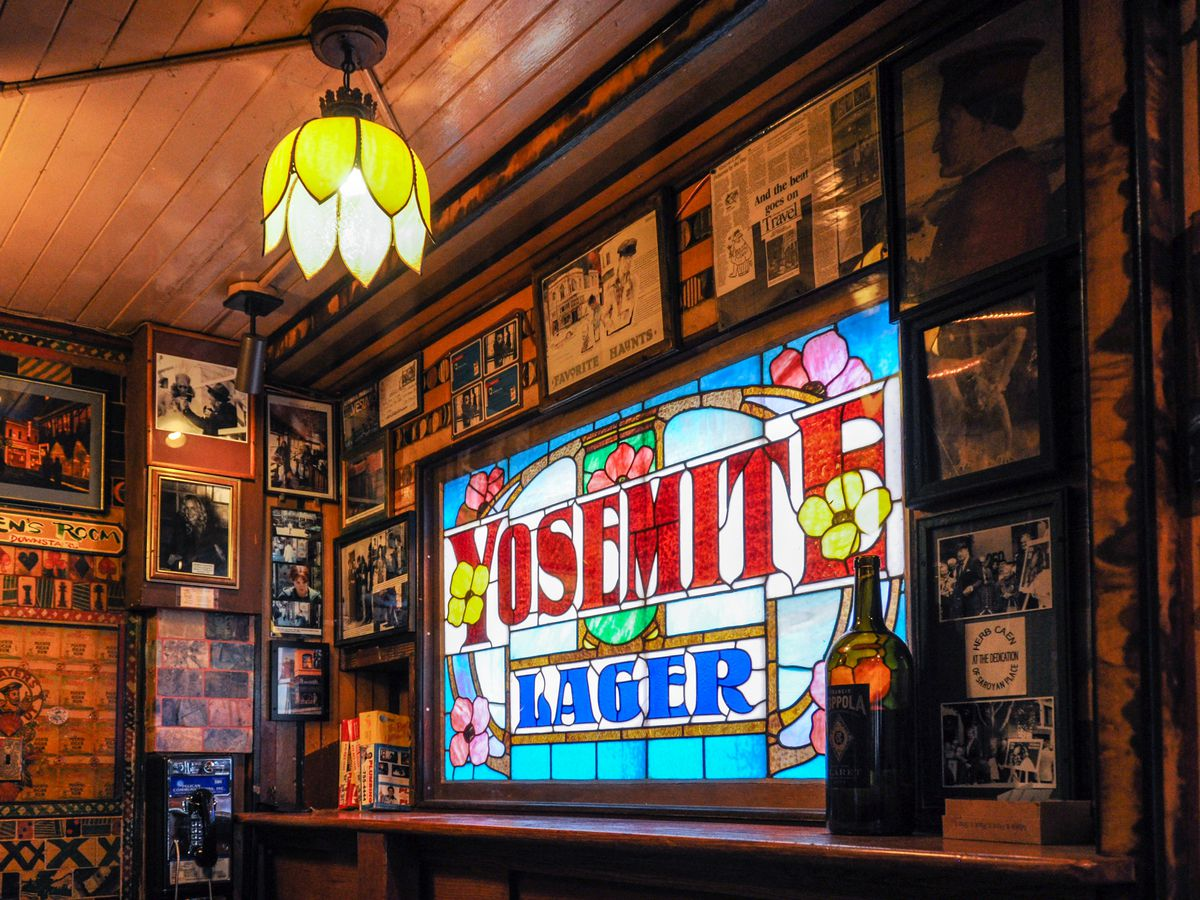 The interior of the Vesuvio Cafe in San Francisco. There is a stained glass window with the words: Yosemite Lager. There are many works of art and photos on the walls.