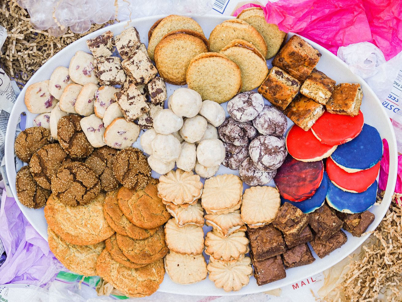 A white oval plate holding 10 different kinds of cookies, surrounded by tissue paper, crumpled-up newspapers, packaging materials, and plastic wrap.