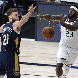 Utah Jazz's Royce O'Neale (23) and New Orleans Pelicans' Nicolo Melli (20) reach for a loose ball during the second half of an NBA basketball game Thursday, July 30, 2020, in Lake Buena Vista, Fla. (AP Photo/Ashley Landis, Pool)