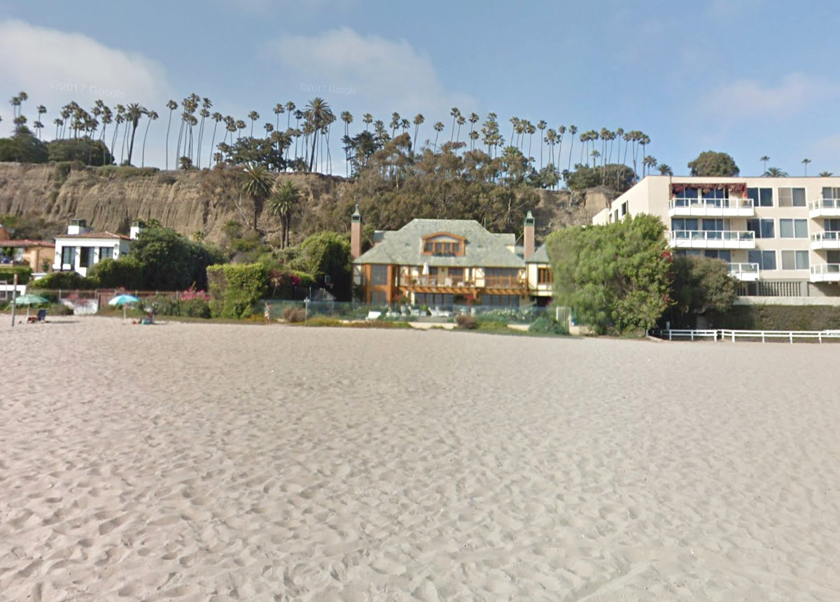 In the foreground is a sandy beach. In the distance is a large beach house and palm trees.