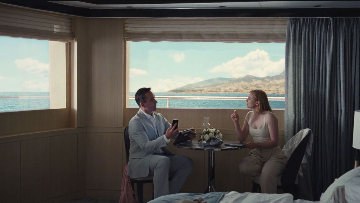 A man and a woman are sitting at a table in a bedroom on a yacht in the HBO show Succession. There are large windows overlooking a body of water and distant mountains. There are gray drapes pulled to the side on one of the windows.