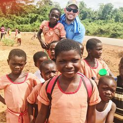 Children in Hiawoanwu, Ghana, gather for a photo with Zach Harding while attending the dedication of a medical clinic.