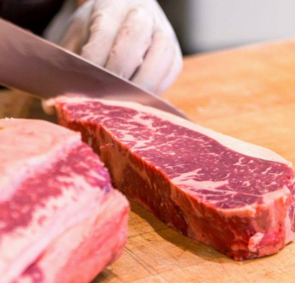 Two steaks with a knife cutting one