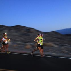 Oswaldo Lopez (near L) of Madera, California and Carlos Alberto of Portugal (near R) run wearing headlamp near Panamint Springs as night falls during the AdventurCORPS Badwater 135