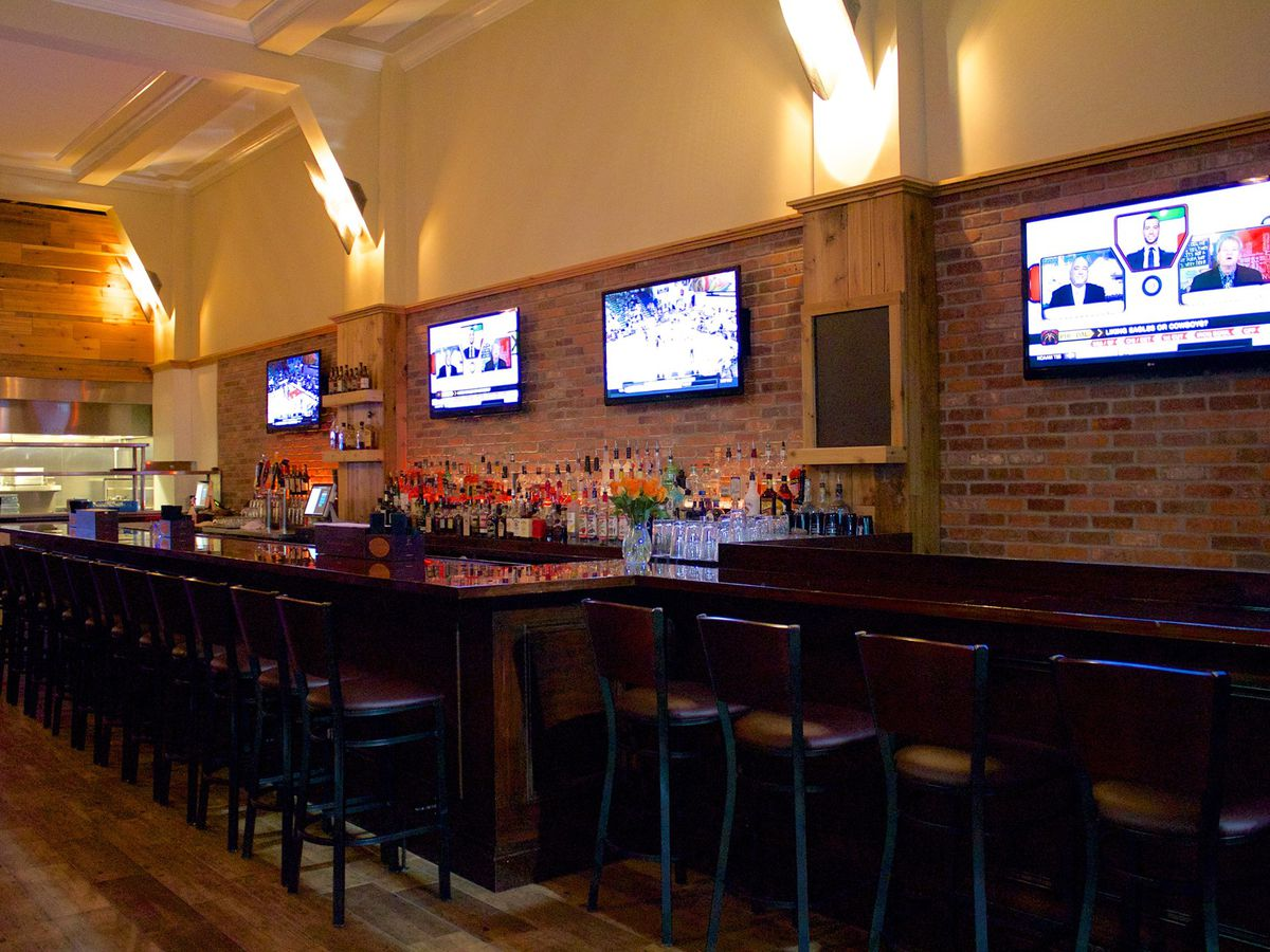 Inside a bar with brick on the walls, low lights, tvs over the wooden bar and wooden chairs