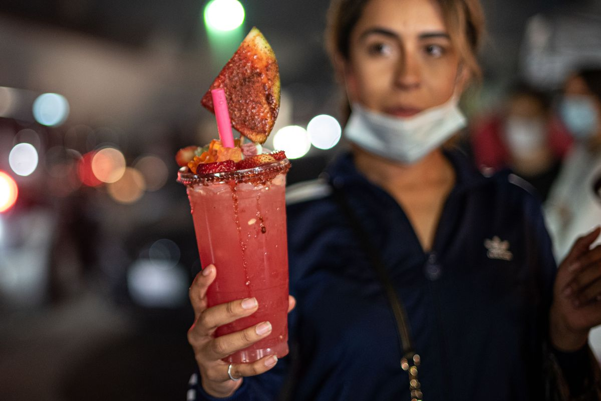 A tall boozy drink with fruit on top at a night market.