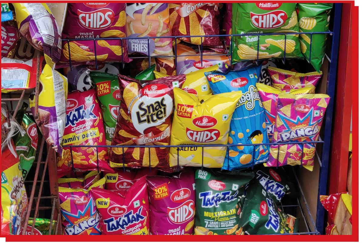 Several colorful and small bags of chips sit in a grocery store display.