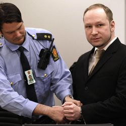 A court officer unlocks the handcuffs of Norwegian Anders Behring Breivik, right, as he appears in court to face terrorism and premeditated murder charges, Oslo, Norway, Monday, April 16, 2012. Breivik, who confessed to killing 77 people in a bomb-and-shooting massacre went on trial in Norway's capital Monday, defiantly rejecting the authority of the court.