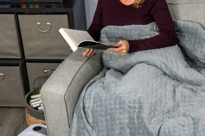 Person curled up on couch under gray blanket, reading a book.